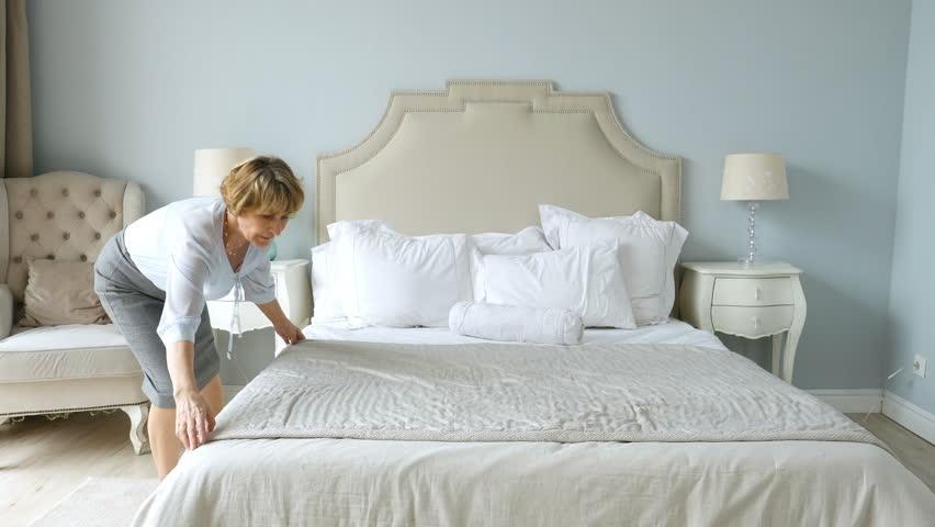 Elderly woman makes the bed in bedroom | Shutterstock HD Video #1022136196
