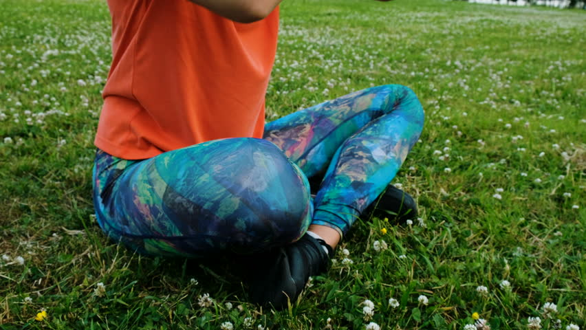 Woman meditates and doing yoga folds her hands in namaste sitting in the lotus position close up on the grass in a city park in nature