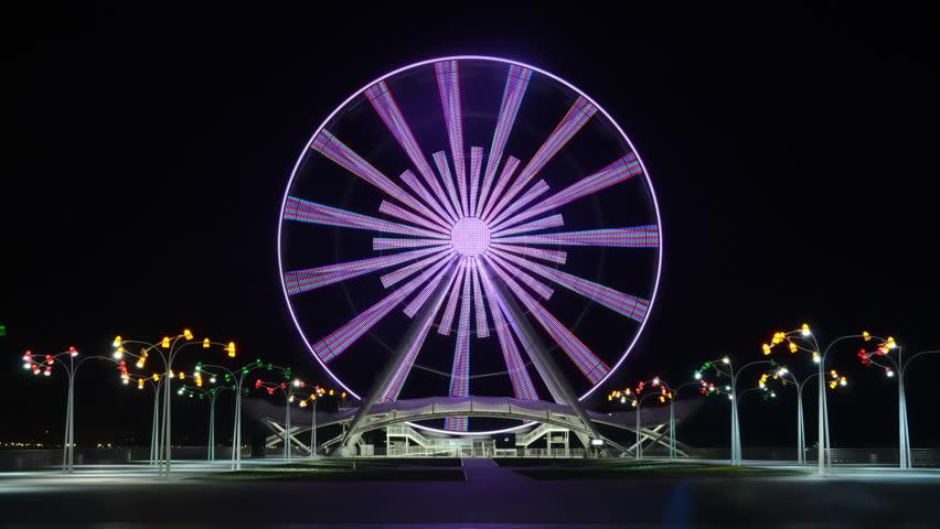 Ferris wheel on the boulevard in Baku, near the Caspian Sea, shot in the evening on a long exposure, with color lighting effects. Azerbaijan.Time lapse video   Shutterstock HD Video #1022172916