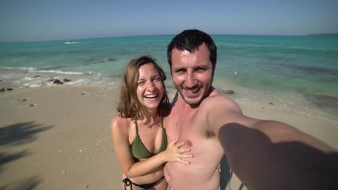 handsome cheerful young couple in love taking selfie on beach. Portrait of carefree tourists enjoying summer vacation. Happy couple on perfect white sand beach on travel holidays.
