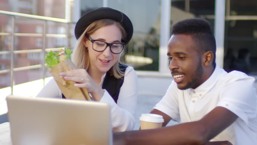 Young blonde woman in fedora hat eating sandwich and discussing project on laptop with male african american coworker while sitting at cafe table on rooftop
