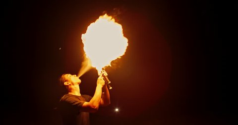 Coll fire show artist having a performance in the dark, juggling sticks with burning ends, then breathing fire on them - slow motion 4k