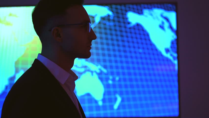 The businessman in glasses standing on the big screen background