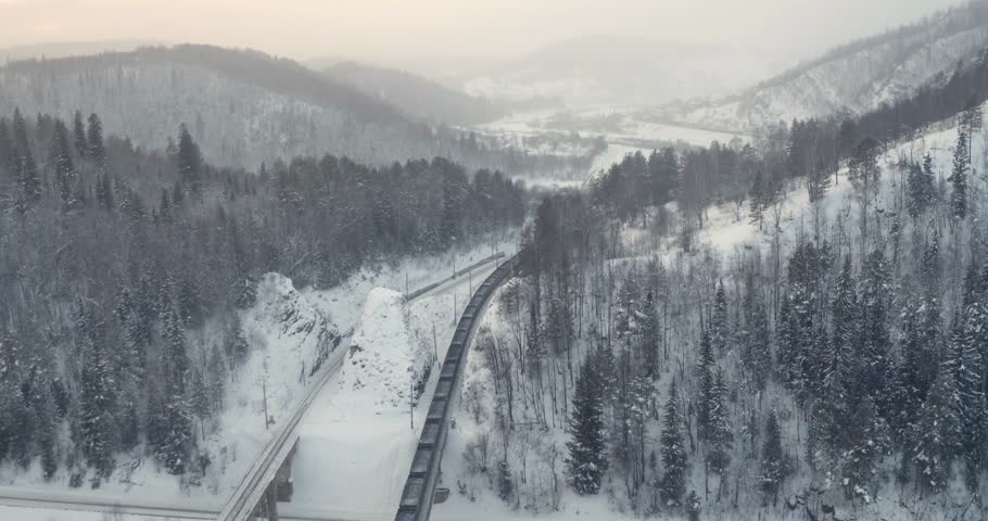 Freight train with coal on Trans Siberian winding two-sided railways near river at winter frozen day in Ural Mountains in Russia - Aerial top view