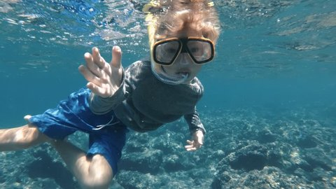 Snorkeling child welcome you to dive with him in clear blue ocean water. Exploring underwater with snorkel, diving mask. Swimming, enjoying adventure in summer vacation