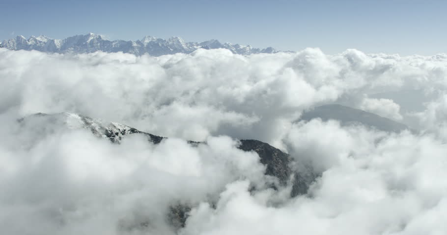 Epic clouds covering himalayan mountains in a wide shot POV aerial over a cold rocky mountain range near Mount Everest Nepal in Tibet