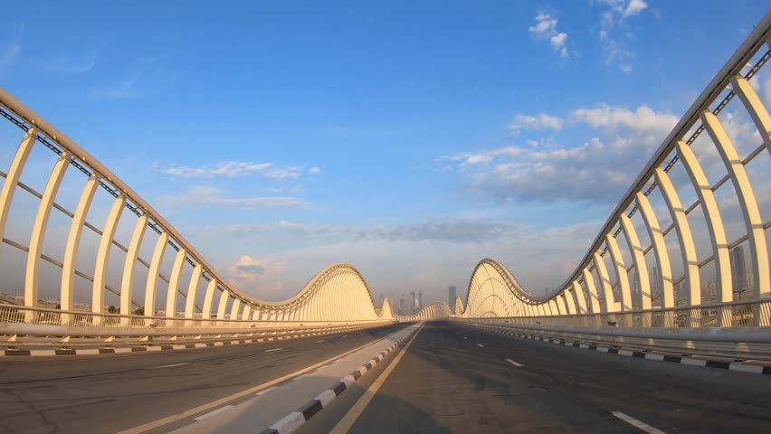 POV Driving on Meydan bridge at sunshine with blue sky and city skyline in the background. Dubai, UAE. | Shutterstock HD Video #1022440276