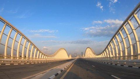 POV Driving on Meydan bridge at sunshine with blue sky and city skyline in the background. Dubai, UAE.