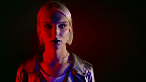 androgynous model with blonde hair is looking forward to camera inside dark room