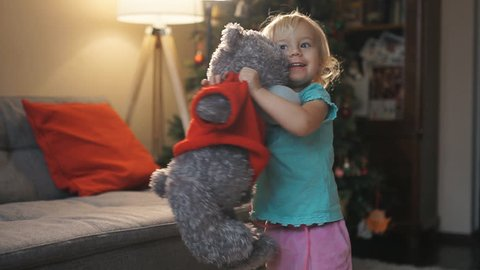 Happy baby girl playing and dancing with soft toy Teddy bear home. Portrait of expressive little girl hugging her plush bear friend, indoor shot. Little girl playing with teddy bear