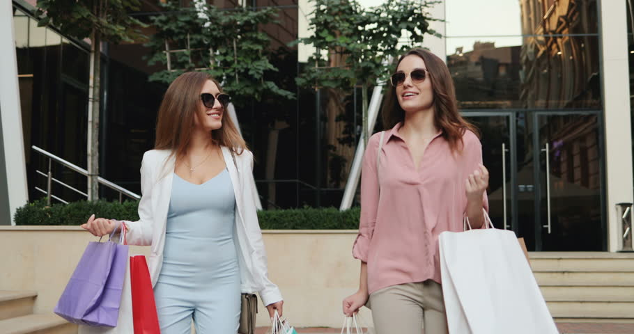 Two happy and stylish young Caucasian girls walking the street with many shopping bags and talking. | Shutterstock HD Video #1022521486