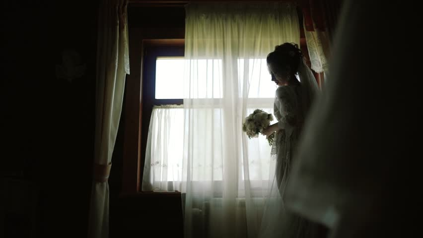 Bride in a white silk dressing gown stay along the panoramic window in wood house | Shutterstock HD Video #1022566846