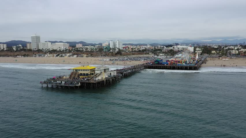 Arial view of Santa Monica pier in Los Angeles, California on an overcast day with the city and coastline in the background   Shutterstock HD Video #1022586496