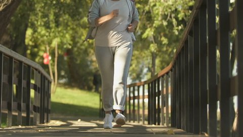 Sport woman feeling sudden knee pain while jogging park, osteoarthritis symptom