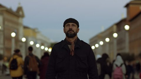 Fashionable Italian man walking in St. Peter's Square in the Vatican at Christmas, with soft sunset natural light. Medium shot on 4k RED camera on gimbal.