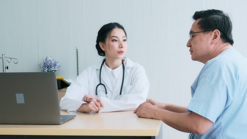 Doctor with patient. Young female medical doctor talking to a senior patient at hospital. Looking at her laptop to discuss medical examination result. Senior care medical and insurance concept. | Shutterstock HD Video #1022636866