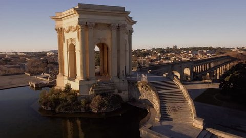 Beautiful sunlight flare flying over water tower in Montpellier Peyrou parc aerial drone shot