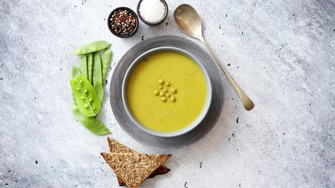 Green pea cream soup in grey bowl placed with spices, fresh peas, full grain bread on stone background. Top view with copy space.