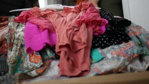 Close up of clothing piling up on bedroom bed - hoarding concept