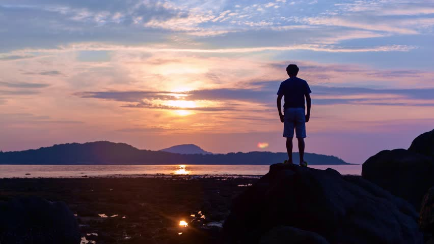 Time lapse of Alone man tourist standing on the stone in tropical sea and enjoying scenery during sunrise or sunset beautiful light dramatic sky environment in phuket thailand #1022726266