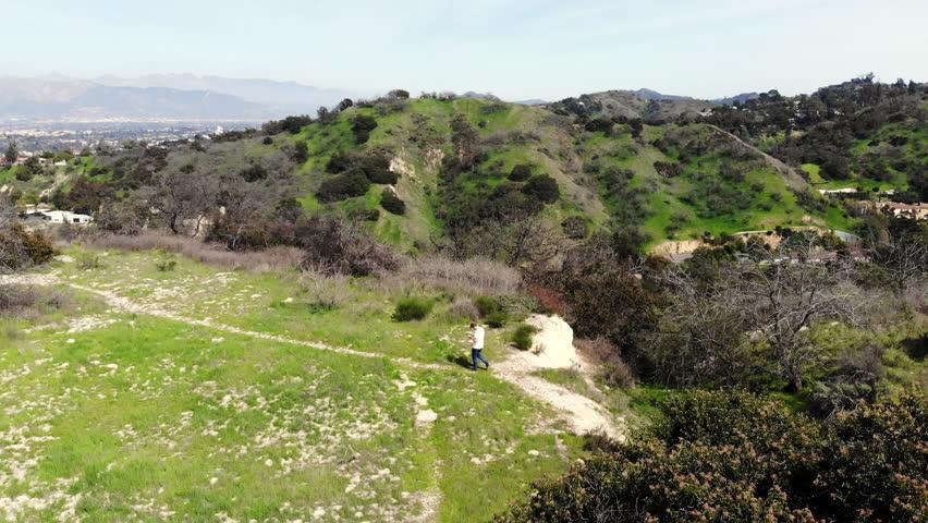 Aerial shot of male walking down a narrow dirt trail on a hill ridge   Shutterstock HD Video #1022730586