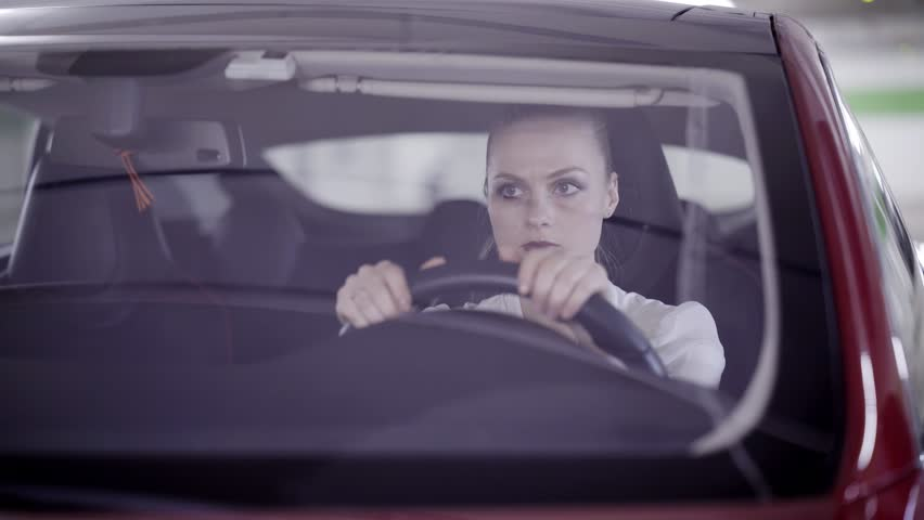 Nice young blonde woman with pony tail wearing white classic shirt is sitting in dark red car behind steering wheel when it's starts smoking outside in underground garage.