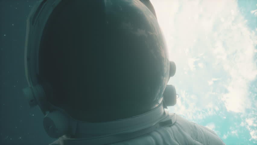 A lone astronaut looks at the planet earth in orbit in outer space, the planet earth reflects in a spacesuit helmet. Cinematic 4k footage for scientific programs on space, planet earth and others
