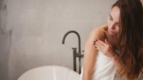 Woman applying cream on her skin in bathroom while siting on bath tub