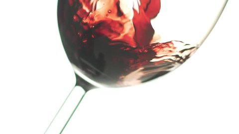 Suggestive slow motion closeup macro shot of pouring an organic excellent red wine in a glass in backlit light. Luxury red wine splashing in slow motion in a wineglass in a white background.