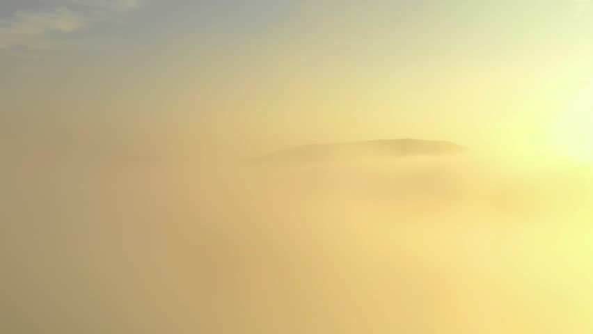 Aerial footage of low clouds in the mountains during sunrise. | Shutterstock HD Video #1022816596
