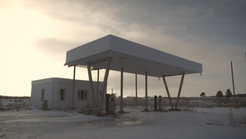 View of derelict gas station next to the road in a winter. Abandoned Petrol Station with No Fuel signs covering the pumps, victim of the economic crisis. The historic route 66.