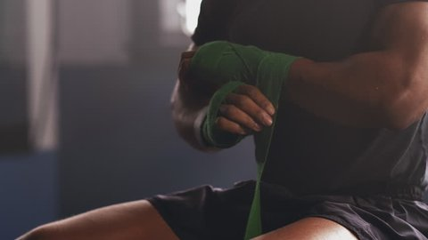 A muscular African American fighter wraps MMA hand wraps around his wrists before training in a boxing gym