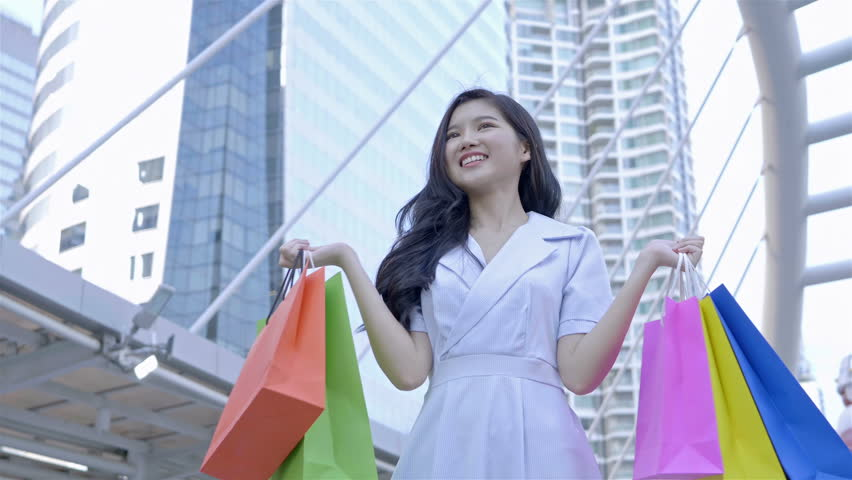 Beautiful Asian woman walks and holding shopping bags smiling happily in city centre Thailand. shopping, happiness and fashion Concept. Slow Motion | Shutterstock HD Video #1022861986