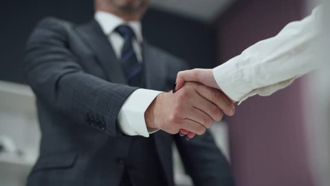 Hiring, man in a suit, a businessman shaking hands with a woman colleague, a handshake in the office.