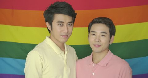 Portrait of young asian gay couple posing in front of gay pride rainbow flag.