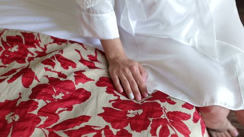 Close-up of the bride in a satin negligee sitting on the bed with red flowers in the hotel, hand close-up.