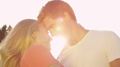 SLOW MOTION, SUN FLARE, CLOSE UP: Happy young woman and her smiling boyfriend rubbing their noses together while on a date in the beautiful sunny nature. Cheerful couple eskimo kissing in summer sun