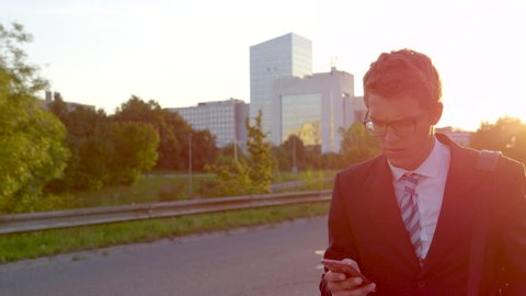 CLOSE UP, SUPER SLOW MOTION, SUN FLARE: Businessman reading a text and getting bad news while walking home at sunset. Caucasian yuppie is surprised and worried as he reads a text on his way from work.