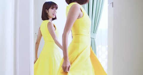 slow motion of asian girl trying dress and looking in mirror cheerful