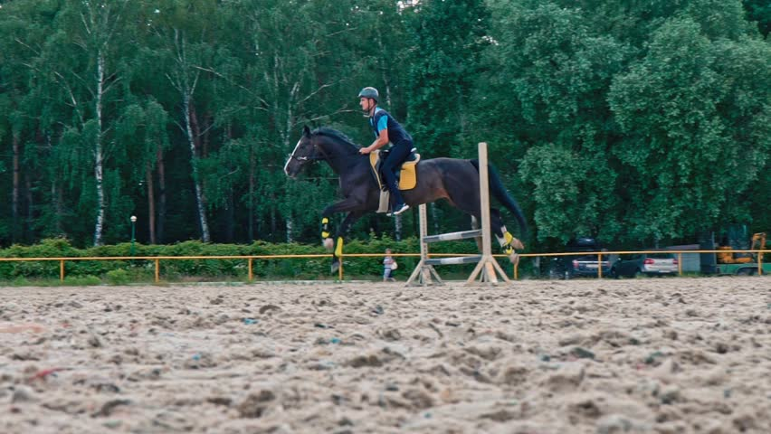 A young man on a horse jumps over obstacles. Slow motion. Training horses before the competition.  Horse Racing. Horse breeding. Farm. Horseman. Rider, equestrian, jockey | Shutterstock HD Video #1022924266