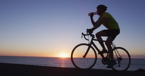 Cyclist athlete man cycling biking training exercise and drinking water. Healthy active lifestyle sports fitness man exercising at sunset. SLOW MOTION RED Cinema Camera.