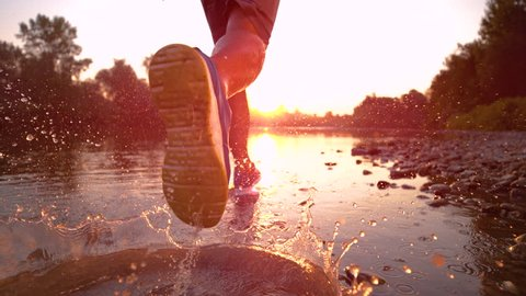 SUPER SLOW MOTION, CLOSE UP, SUN FLARE: Golden evening sunbeams shine on athletic young man jogging along the tranquil river. Picturesque serene nature surrounds sportsman running in the shallow water