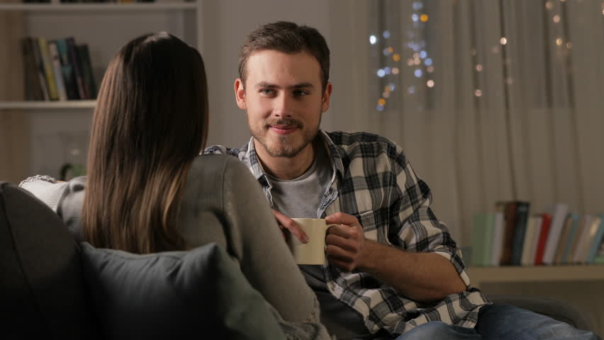 Happy couple talking and drinking coffee sitting on a couch in the night at home | Shutterstock HD Video #1022987146