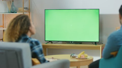 Happy Couple Sitting At Home in the Living Room Watching Green Chroma Key Screen TV, Relaxing on a Couch. Couple Room Watching Sports Match, News, Show or a Movie.