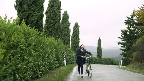 Content Italian man walking along the street with a bike while looking at the trees alongside the road on an overcast day. Wide shot on 8k helium RED camera.