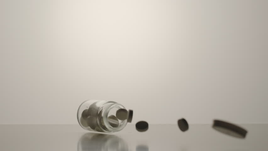 SLOW MOTION: Silhouette of Pills fall down from the glass box and fly around on the white surface | Shutterstock HD Video #1023062506