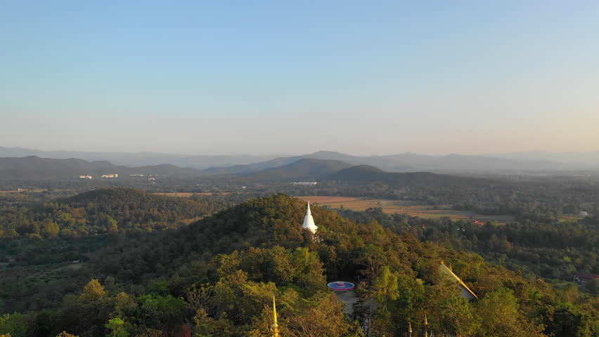 Aerial view Thailand temple with giant gold buddha statue on top of mountain hill on background scenery mountain landscape at sunset   Shutterstock HD Video #1023080056