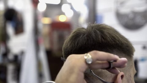 Close-up of hairdresser cuts man's head. Male hairdresser makes short haircut for men using professional hairdressing scissors. Hairdressing skills and men's haircuts