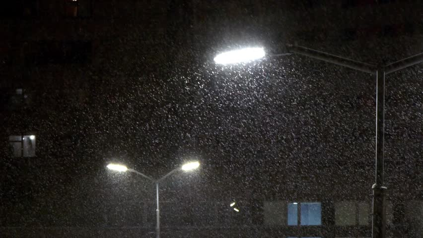 Shines a street lamp. Snow falls at night. Night empty street in winter.