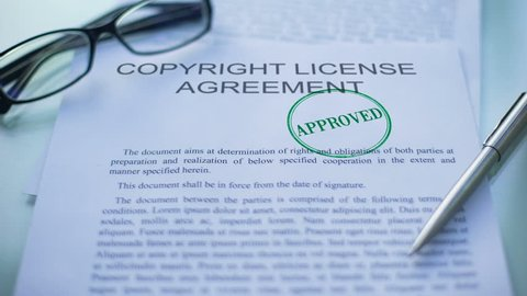 Copyright license agreement approved, officials hand stamping seal on document